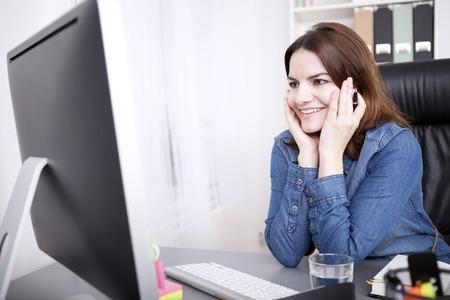 carita feliz: Cierre de Oficina Feliz Mujer que se inclina sobre la mesa con las manos en su cara, mirando a la pantalla del ordenador. Foto de archivo