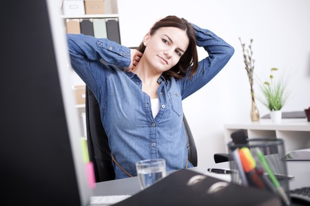 working stiff: Exhausted Young Office Woman Sitting at her Office, Holding her Head and Neck While Looking at Computer Screen. Stock Photo