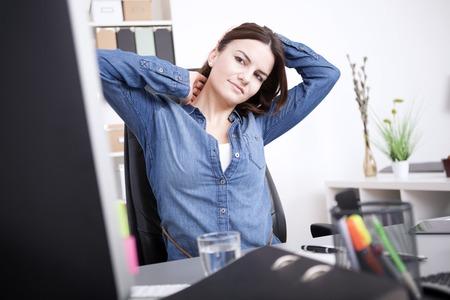 Uitgeputte Jonge Office vrouw zit op haar bureau, met haar hoofd en nek tijdens het kijken naar het computerscherm. Stockfoto - 38262902