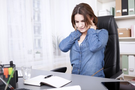 Close up Tired Office Woman Sitting at her Desk, Massaging the Back of her Neck Seriously While Looking at the Notebook and Pen on the Table. Stock Photo