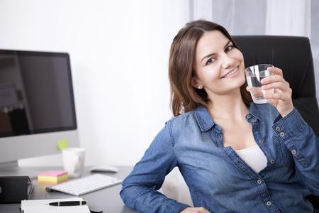 Close-up Jonge volwassen Office Ontspannen van de Vrouw op haar stoel terwijl een glas water en kijken naar de camera.