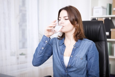long sleeves: Close up Young Woman in Denim Long Sleeves Shirt Sitting on Office Chair While Drinking a Glass of Water
