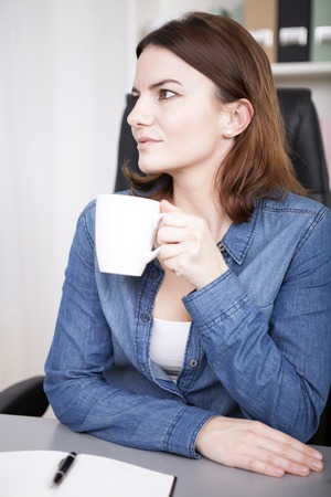 observant: Observant young businesswoman drinking coffee at her desk with the mug in her hands staring off to the side with an attentive expression Stock Photo