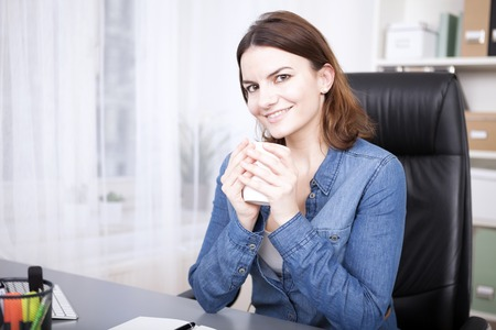 Attractive confident businesswoman with a friendly smile sitting at her desk cradling a cup of coffee i her hands as she takes a coffee break photo