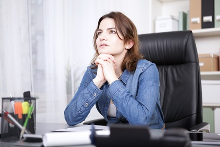 Businesswoman striving for a solution to a problem sitting at her desk with her chin on her hands looking into the air with a serious contemplative expression