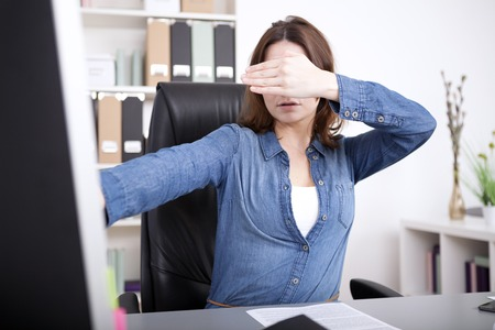visualise: Businesswoman covering her eyes as she sits working at her desktop computer in the office as she tries to visualise a concept or new idea