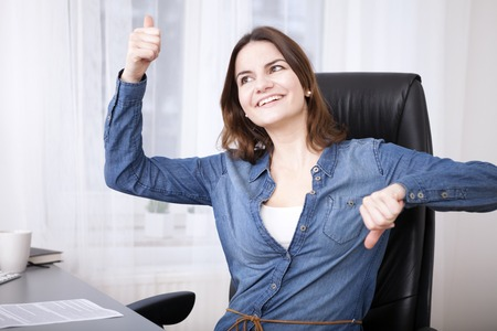 simultaneously: Undecided businesswoman laughing playfully and giving a thumbs up and down gesture simultaneously Stock Photo