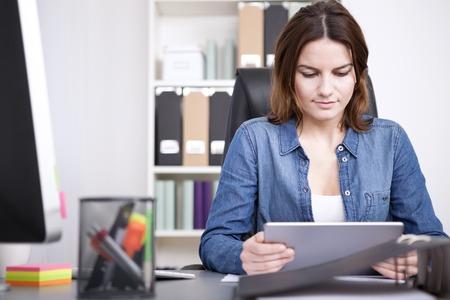 Zakenvrouw lezen van informatie op haar tablet pc als ze zit op haar bureau in het kantoor met een ernstige uitdrukking in beslag genomen