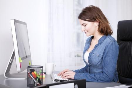 Lachend zakenvrouw het invoeren van gegevens voor haar desktop computer zitten te typen op het toetsenbord, zijaanzicht Stockfoto - 38263016