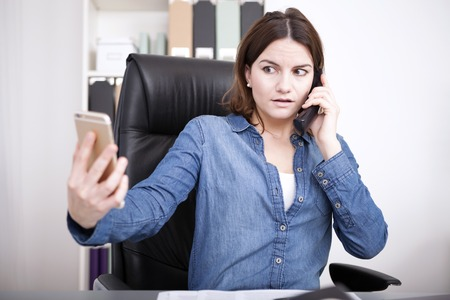 Businesswoman talking on the land line telephone phone in the office while simultaneously checking her mobile with a worried expression photo