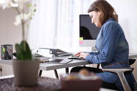 Besetzt Hübsche junge Geschäftsfrau in Denim Bluse sitzt an ihrem Arbeitstisch mit Dokumenten und elektronischen Geräten.