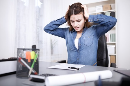 anguished: Stressed businesswoman under pressure sitting holding her head with her hands with an anguished expression as she eyes unfinished paperwork on her desk Stock Photo