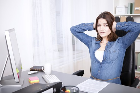 anguished: Stressed overworked young businesswoman sitting at her desk with her hands raised to her head and an anguished expression Stock Photo