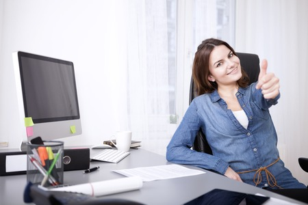 Smiling successful businesswoman giving a thumbs up gesture of success and approval as she sits at her desk in the office Standard-Bild
