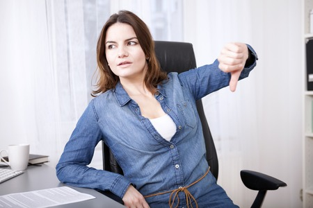 Businesswoman sitting at her desk in the office giving a thumbs down gesture with a serious expression indicating, failure, a negative, voting something down or disapproval photo