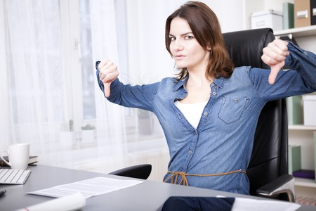 emphatic: Businesswoman giving an emphatic thumbs down gesture with both hands and frowning at the camera depicting disapproval, a failure, voting something down or disagreement