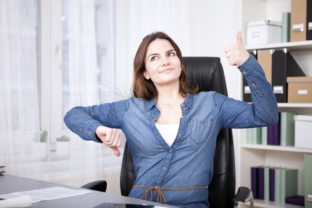 Close up Thoughtful Young Office Woman Sitting on her Chair Showing Thumbs Up and Down Hand Signs While Looking Up. Stockfoto
