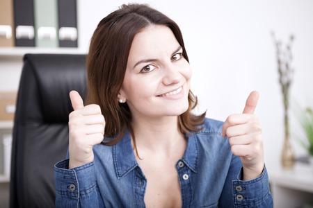 Gelukkig triomfantelijke zakenvrouw het geven van een thumbs up gebaar met beide handen om haar succes te signaleren, terwijl kijken naar de camera met een stralend vriendelijke glimlach Stockfoto