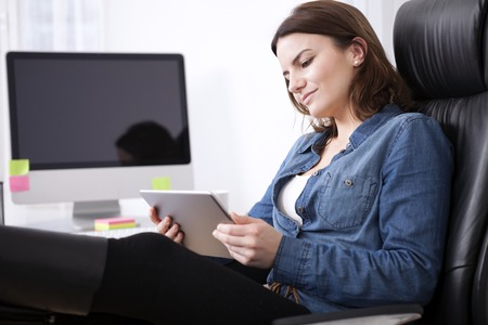head tilted: Puzzled businesswoman sitting in her office chair studying her tablet screen with her head tilted to the side and a serious expression