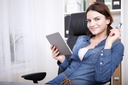 Aantrekkelijke zakenvrouw werkt op een tablet-computer in het kantoor zitten in een ontspannen positie in haar stoel bij de camera glimlacht