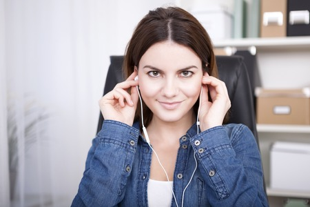 Businesswoman sitting listening to music or a recording on a set of earplugs looking directly into the lens with a warm friendly smile