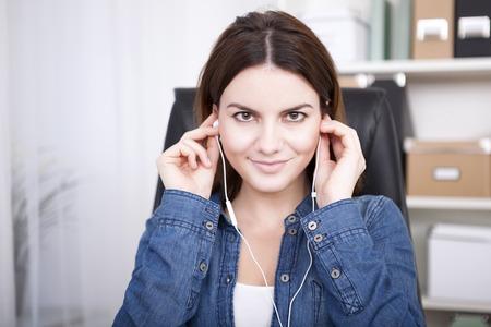 Zakenvrouw zitten luisteren naar muziek of een opname van een set oordopjes die direct in de lens met een warme en vriendelijke glimlach