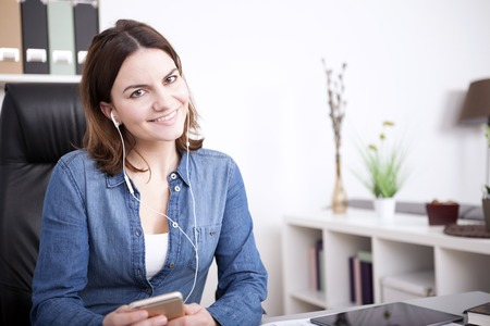 phonecall: Close up Smiling Pretty Office Woman Listening to Music From Mobile Phone Using Headphone While Looking at the Camera. Stock Photo