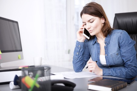 Serious businesswoman listening to a telephonephone call at her desk reading peperwork in front of her as she listens photo