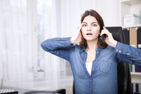 reacting: Businesswoman reacting in shock to a phone call sitting at her dek with a wide eyed expression and her hand to her face Stock Photo