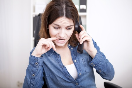 Frantic businesswoman making a phone call frowning and biting her nails as she listens to the conversation photo