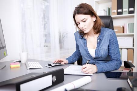 Hardwerkende zakenvrouw zit aan haar bureau in het kantoor van het schrijven van een rapport en het doen van berekeningen op een handmatige rekenmachine Stockfoto - 38263140