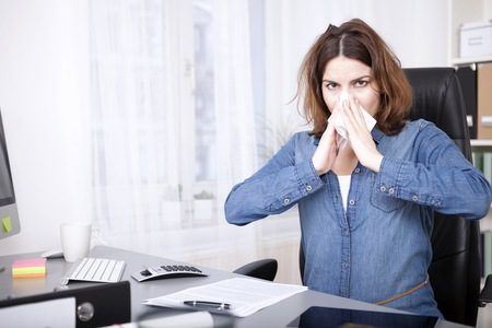 hanky: Young businesswoman with dishevelled hair with a cold and flu sitting at her desk in the office blowing her nose on a tissue