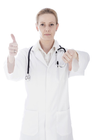 Close up Portrait of a Serious Woman Doctor Showing Thumbs Up and Down Hand Signs While Looking at the Camera. Isolated on White Background. photo