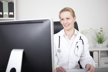 Happy Female Medical Doctor with Stethoscope on her Shoulders Looking at her Computer Screen While Sitting at her Office. photo