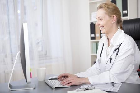 Gelukkig volwassen vrouw arts zittend aan haar bureau tijdens het chatten op haar Patiënten met behulp van haar computer op de tabel.