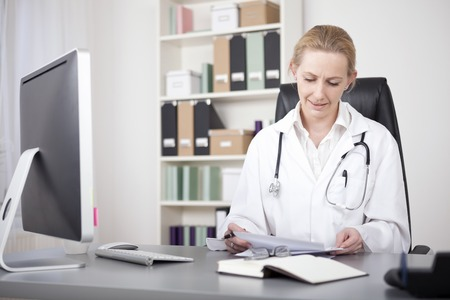 Adult Female Doctor Sitting at her Office and Reviewing her Written Findings on White Paper Standard-Bild