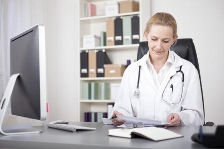 Adult vrouwelijke arts zitten op haar kantoor en het beoordelen van haar schriftelijke Bevindingen over het Witboek