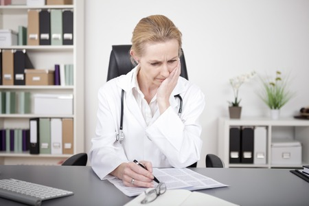 doctor care: Thoughtful Adult Female Doctor Studying Medical Findings on a Paper While Sitting at her Table