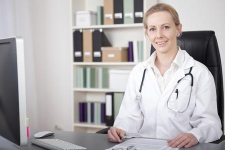 Close-up Glimlachende Vrouwelijke Arts met stethoscoop op haar schouders, zit op haar bureau met documenten en Kijkend naar de camera. Stockfoto