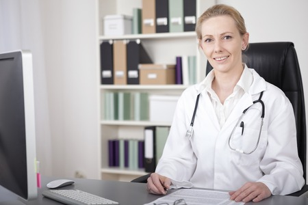 Close up Smiling Female Physician, with Stethoscope on her Shoulders, Sitting at her Desk with Documents and Looking at the Camera.