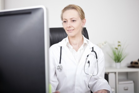 Close up Blond Woman Doctor with Stethoscope Apparatus on her Shoulders Sitting at her Office While Facing the Computer Monitor. photo