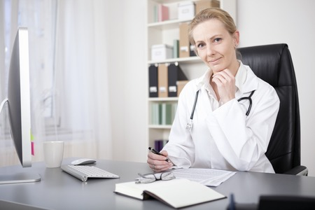 Smiling Blond Female Doctor Sitting at her Table, with Pen and Paper to Make Diagnosis, and Looking at the Camera with Hand on her Chin. photo