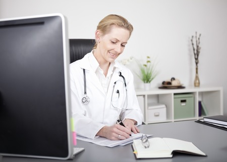 findings: Smiling Female Doctor with Stethoscope on her Shoulders Writing Some Medical Findings While Sitting at her Table. Stock Photo
