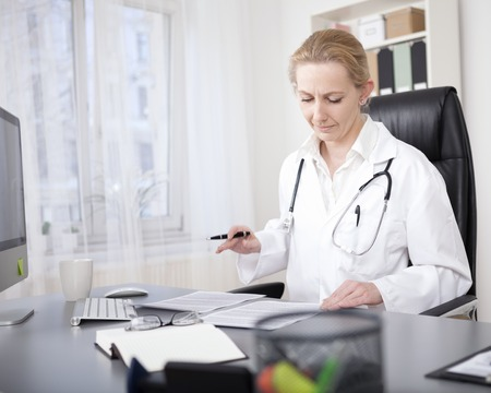 clinician: Adult Female Clinician Sitting at her Desk and Reading Back her Written Medical Reports Seriously.
