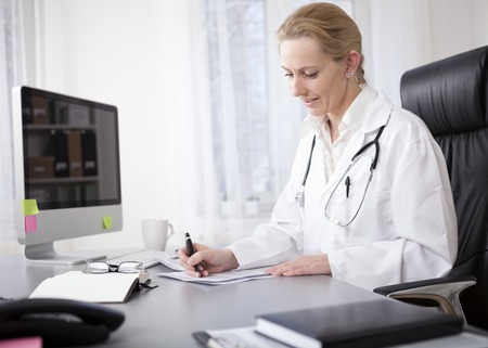 Serious Adult Woman Doctor with Stethoscope on her Shoulders Writing Some Medical Findings on a Paper at her Worktable.