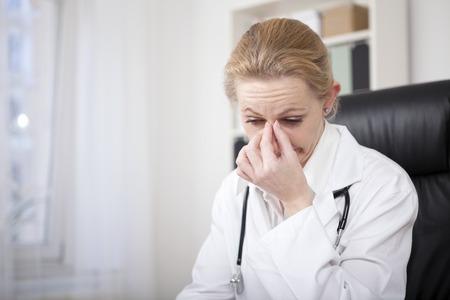 Close up Stressed Adulte Femme médecin assis à son bureau et Tenant son pont de nez tout en regardant vers le bas Banque d'images