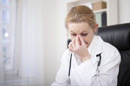 Close-up Stressed volwassen vrouwelijke arts zitten aan haar bureau en houdt haar neus Bridge Terwijl Omlaag kijken Stockfoto
