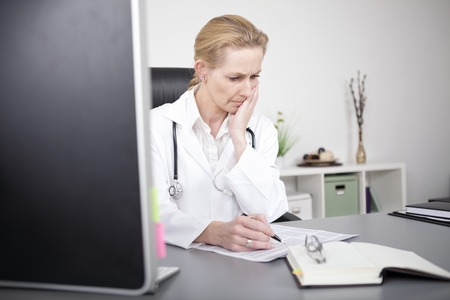 clinician: Adult Female Clinician Sitting at her Office and Reading Medical Reports Seriously While Leaning on her One Hand. Stock Photo