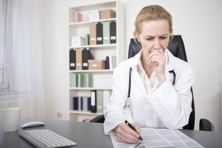 Serious Adult Female Medical Doctor Reading Medical Documents on the Table with One Hand on her Face and the Other is Holding a Pen. Standard-Bild