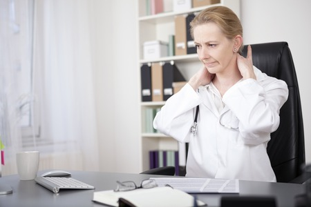 Tired Female Medical Doctor Sitting at her Office and Massaging the Back of her Neck While Looking Down. photo